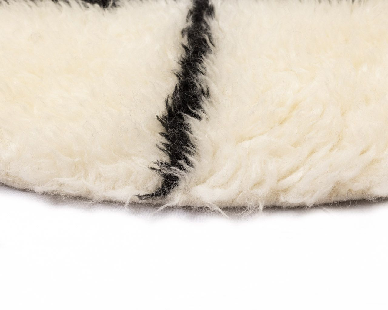 white round rug in black square patterns