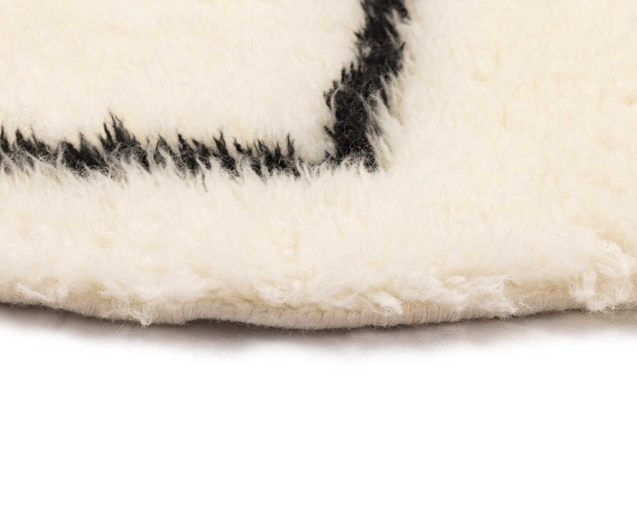 feathery round rug in white with black rhombus