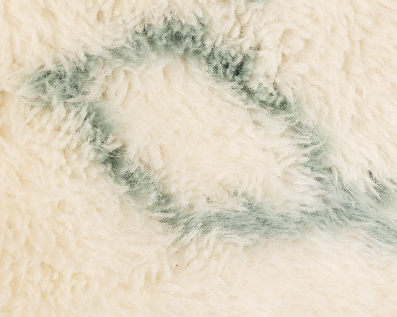 simple rectangular white rug with green symbol fringes